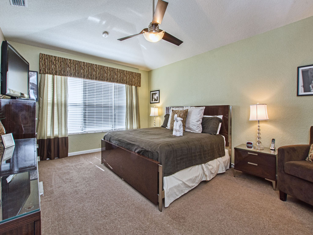Master suite number one features a overhead ceiling fan.