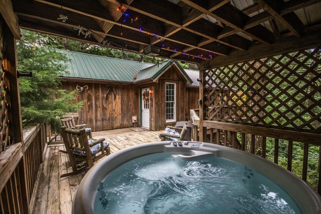Modern hot tub just a few feet from the front door with gazebo overhead