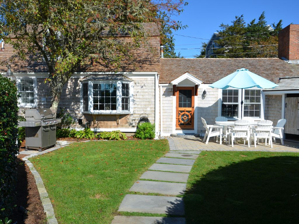 Rear yard with sunny patio, roomy outdoor shower and a large Weber gas grill.
