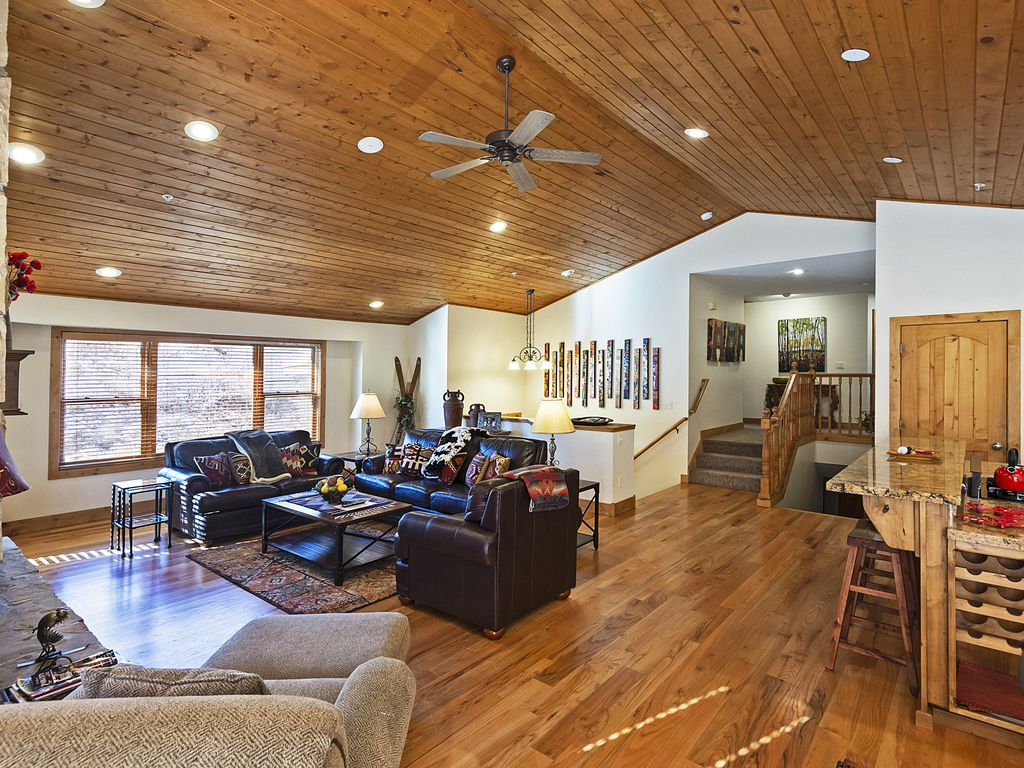Living area with gas during fireplace, TV, kitchen and dining
