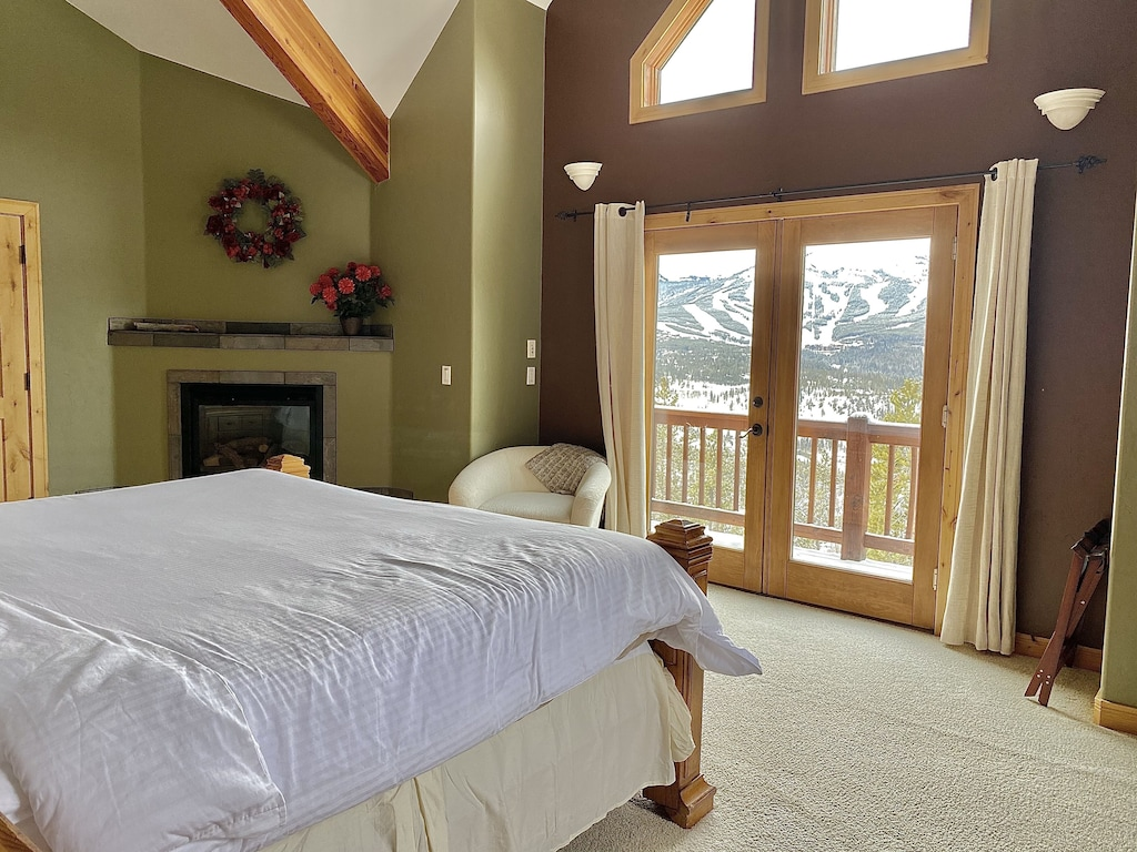 Upper Level Bedroom 1 - Upper level bedroom with king bed, private deck, private bath, fireplace and sunset mountain views