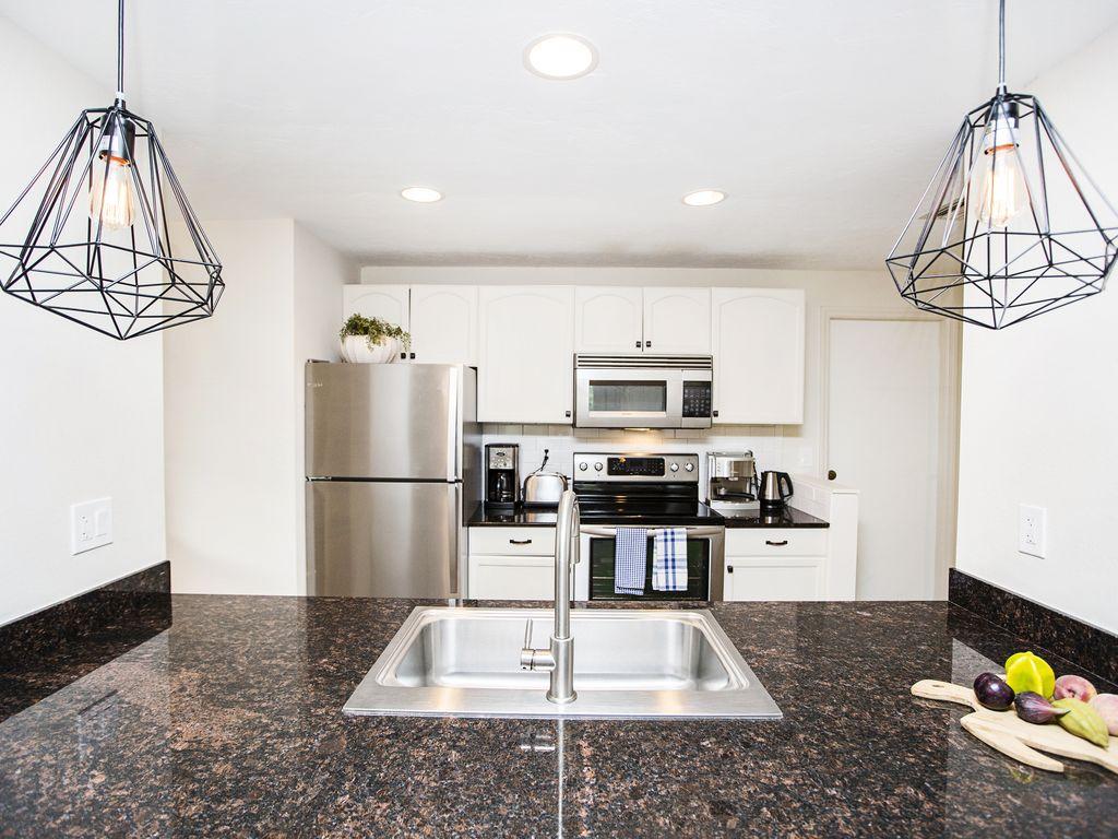 Die Küche ist ausgestattet mit modernen Edelstahlgeräten und einer Steinplatte