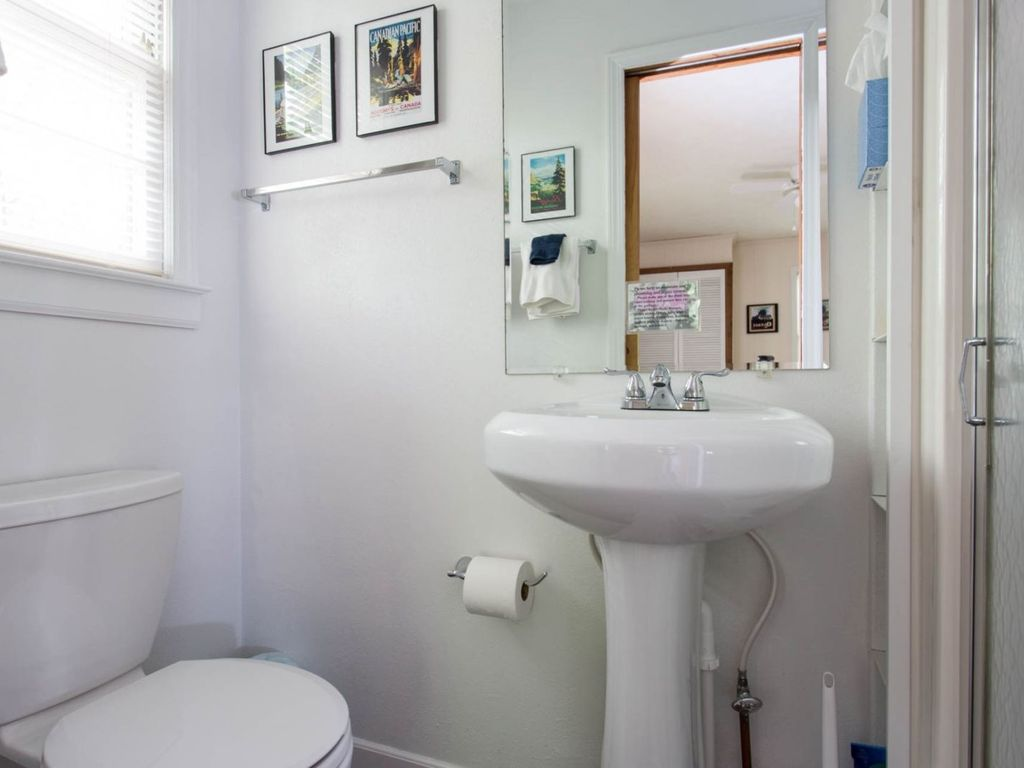 The bathroom has a walk-in shower and pedestal sink.