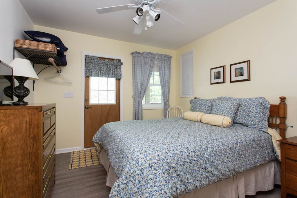 The third bedroom has a bureau, TV, window, ceiling fan, and door to the front of the home.