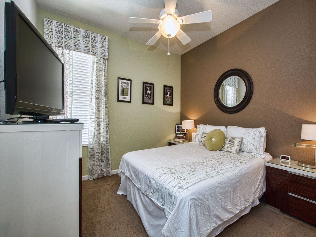 Downstairs bedroom features a queen bed and view of pool.