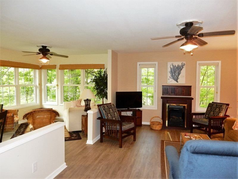The living area features a gas fireplace. The warm wood floors are throughout the home.