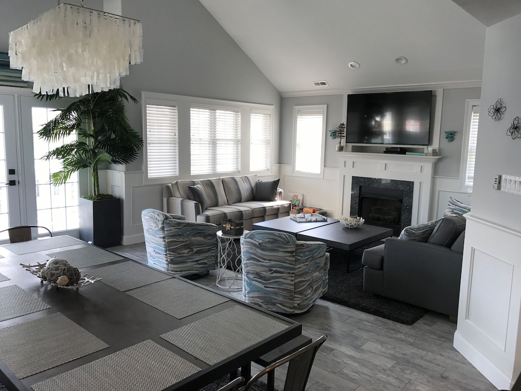 """Cathedral ceilings make this open living space feel even bigger with it's 65"""" TV"""
