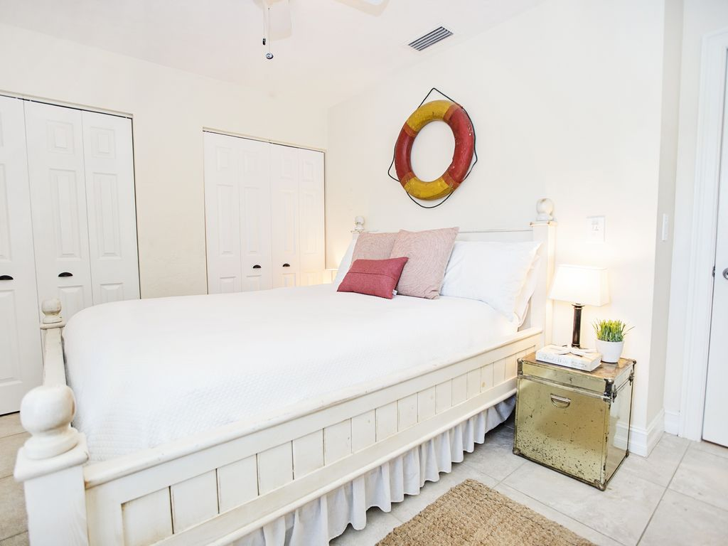 Nautical style guest bedroom with a queen size bed and pool-view.