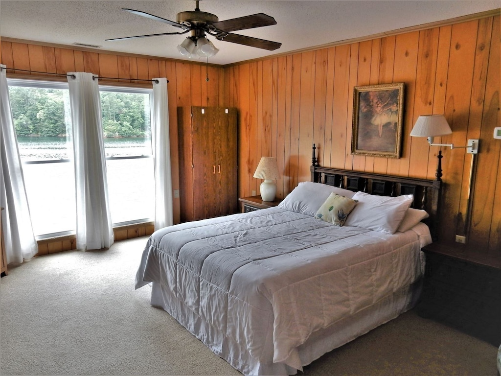 The fourth bedroom has large windows and TV.