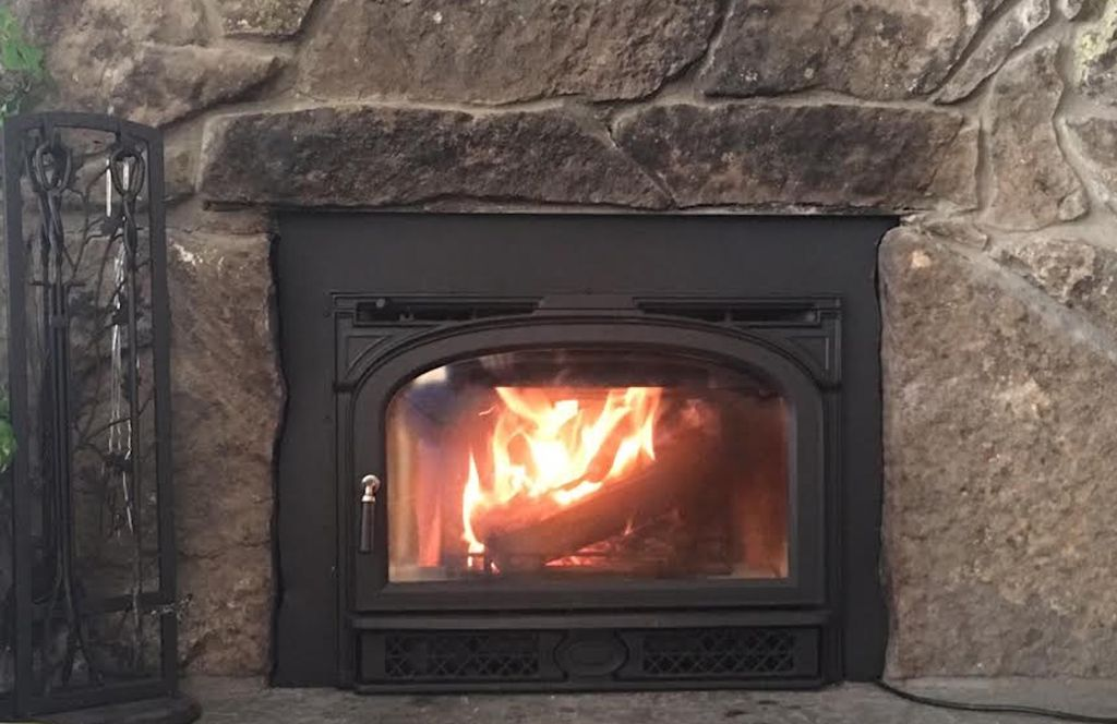 New wood-burning stove insert in fireplace