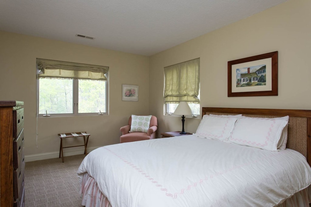 One of the bedrooms has a queen bed with a cozy chair, bureau, and windows.