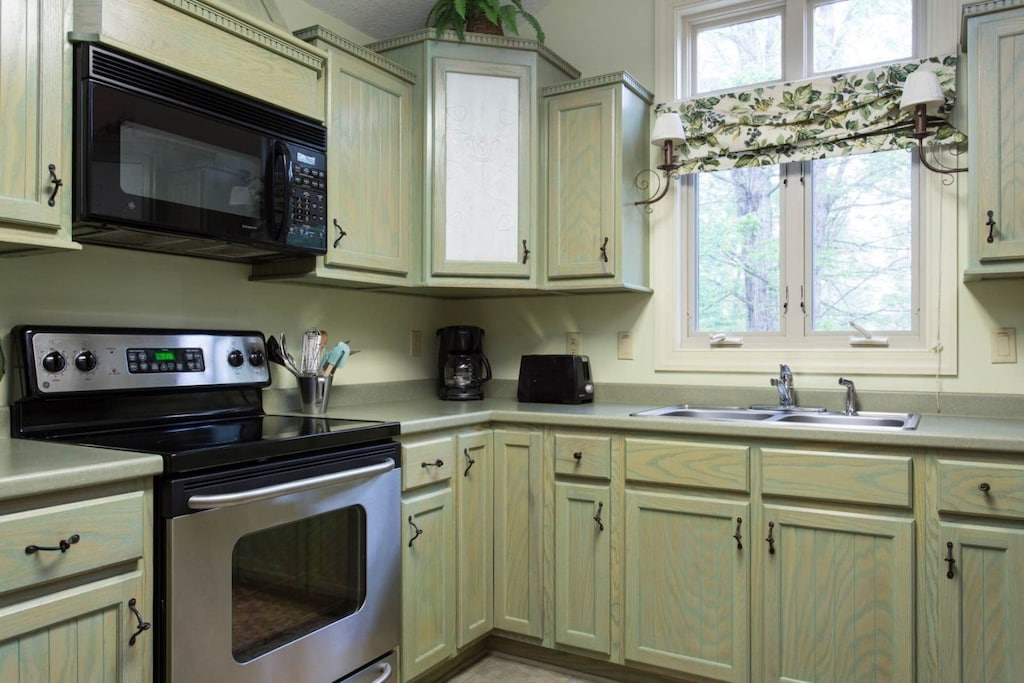 There is a smooth-top electric range and microwave above it. The dishwasher is on the opposite side of the U-shaped kitchen.