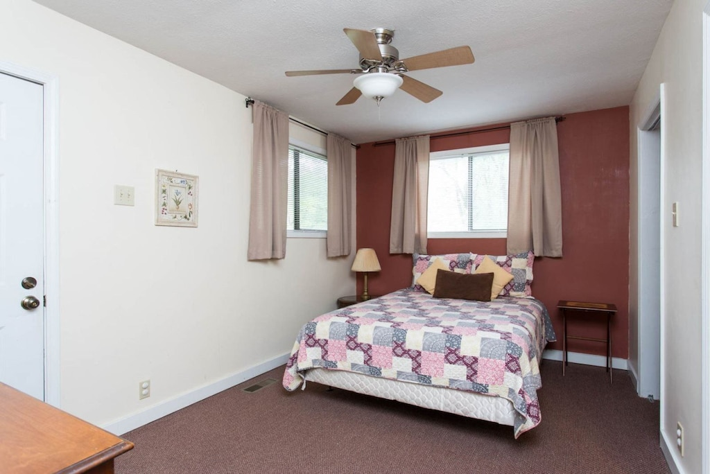 There are windows in the bedroom, a ceiling fan, and a door that leads to a covered deck.