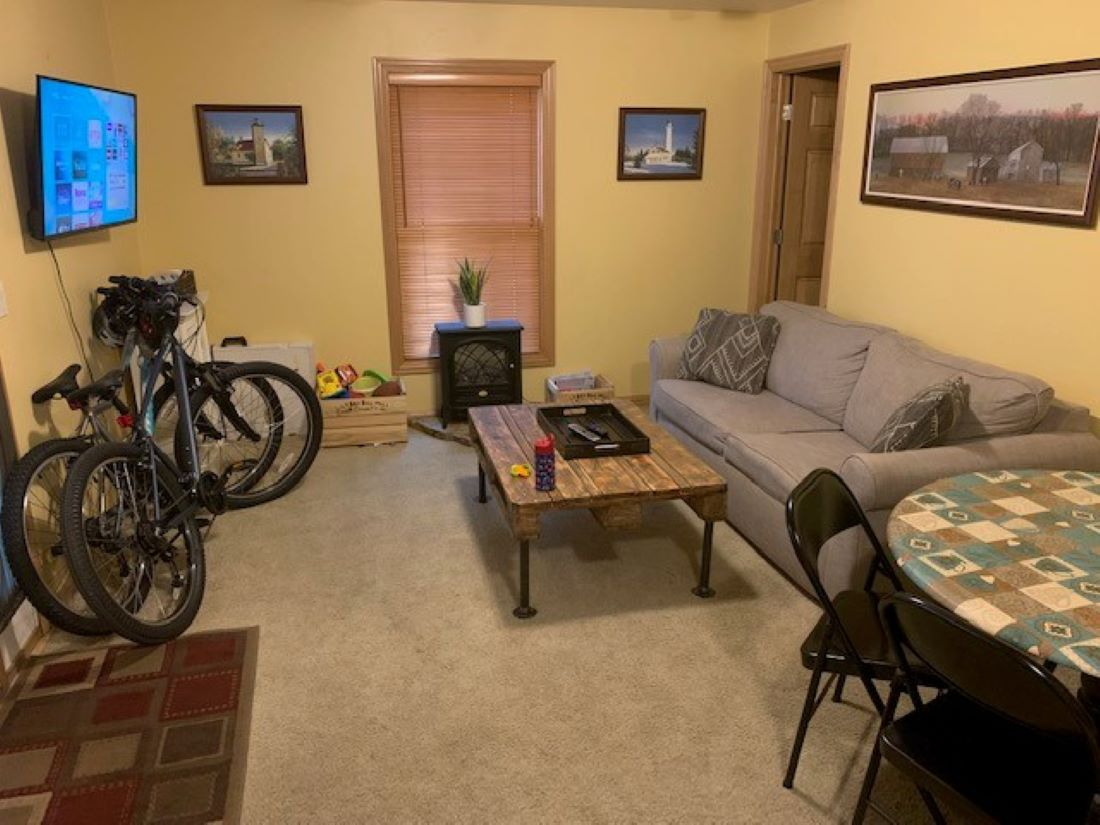 Cozy living room with couch, table, RokuTV, 2 bikes, and games.