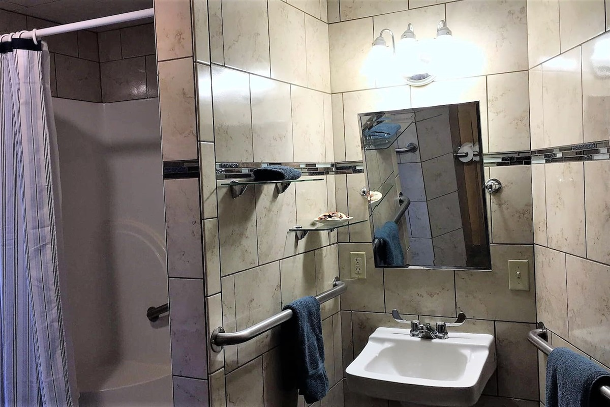 Handicapped accessible bathroom, fully tiled with stall shower