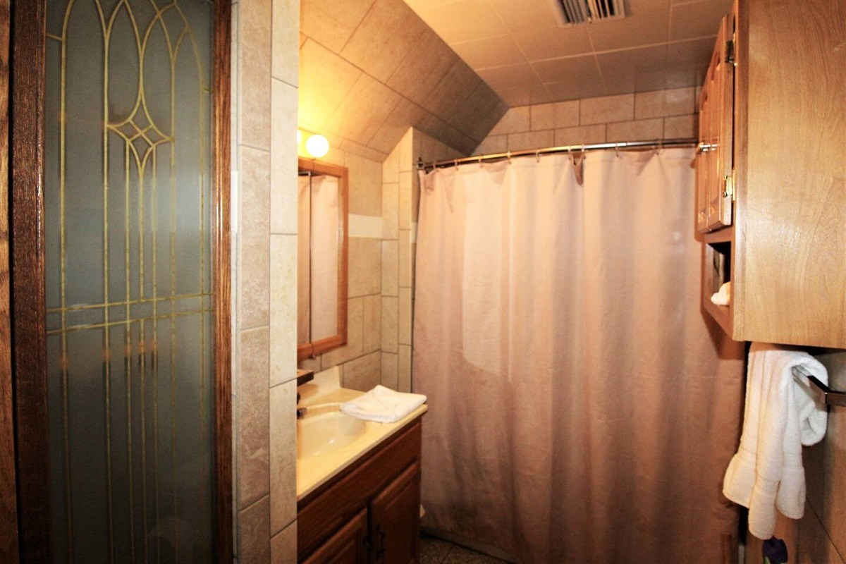 Full bathroom, fully tiled, with tub/shower combination