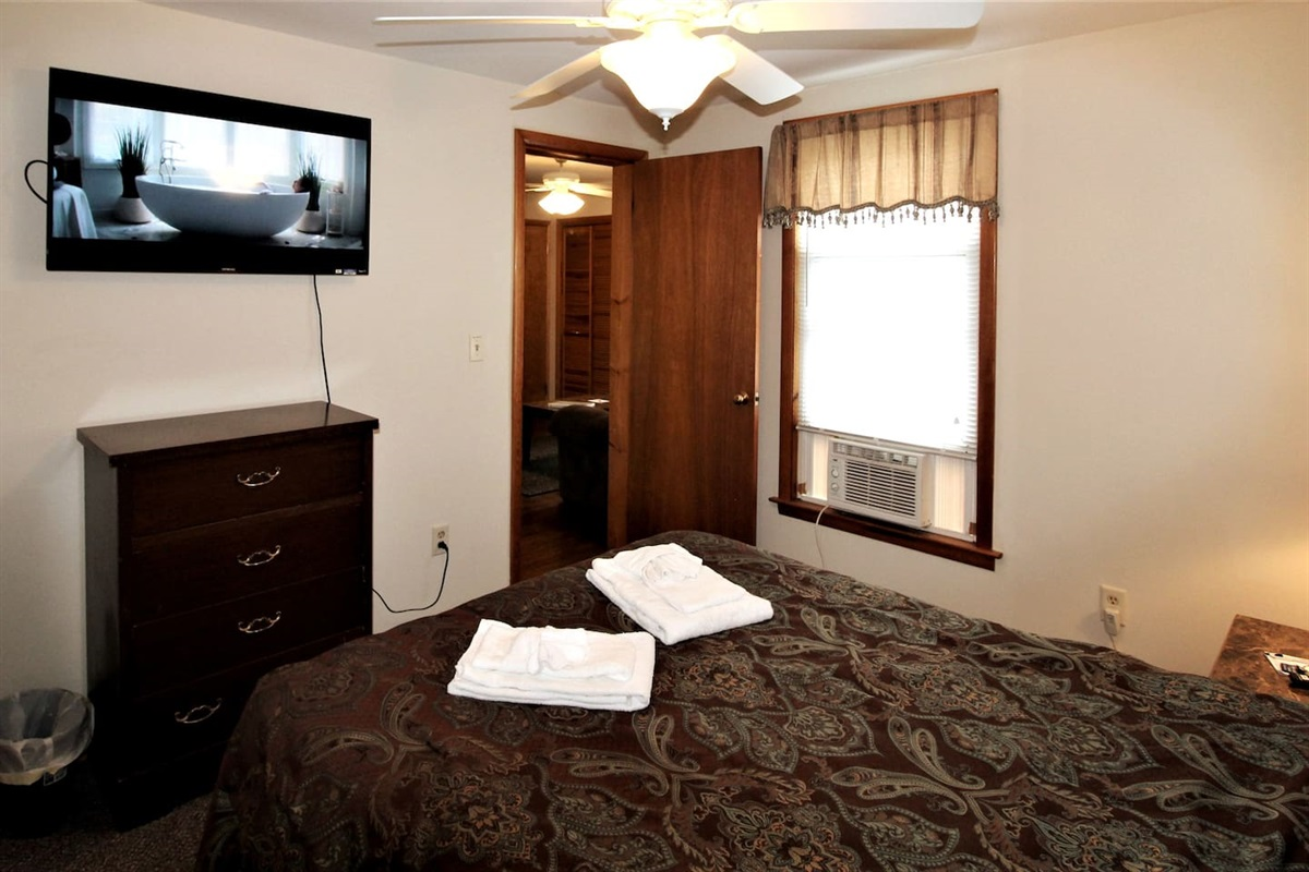 The comfortable bedroom features a wall mounted flat screen smart Roku TV for relaxing after a long day at the ballpark or sightseeing
