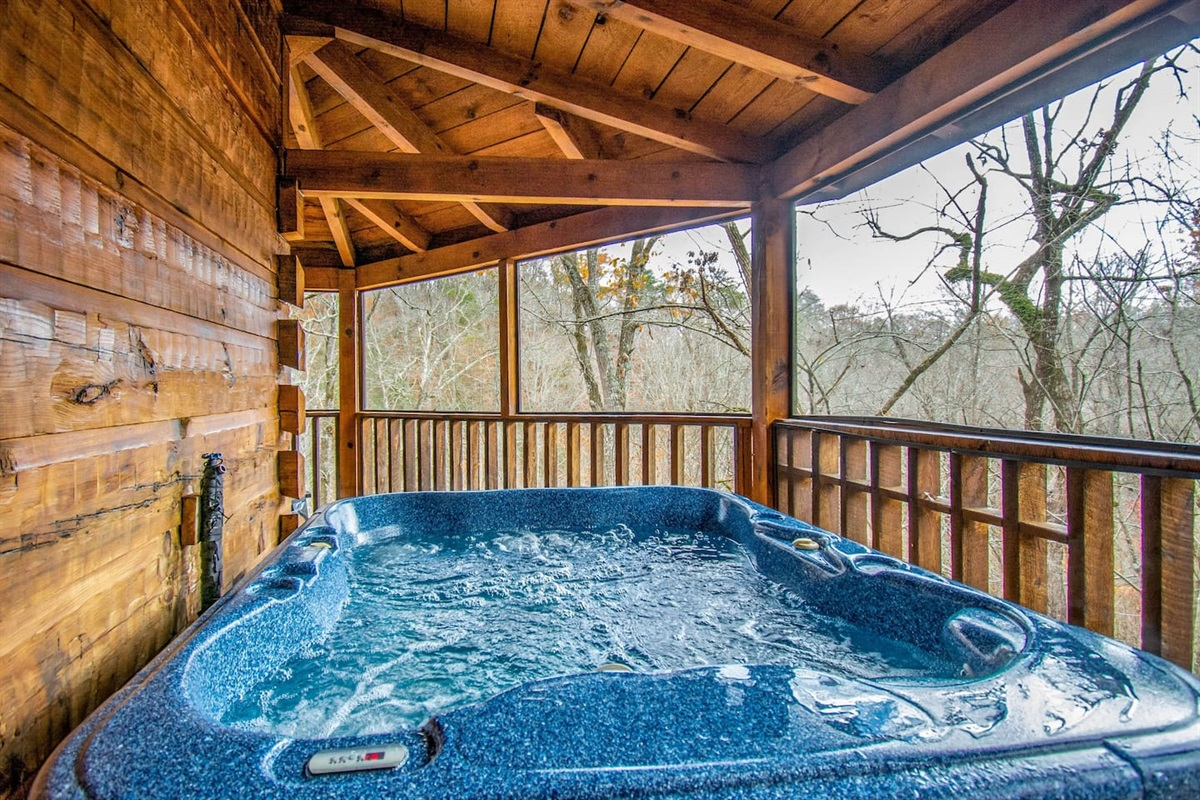 The hot tub is just outside of the main level bedroom in a screened in section of the deck.