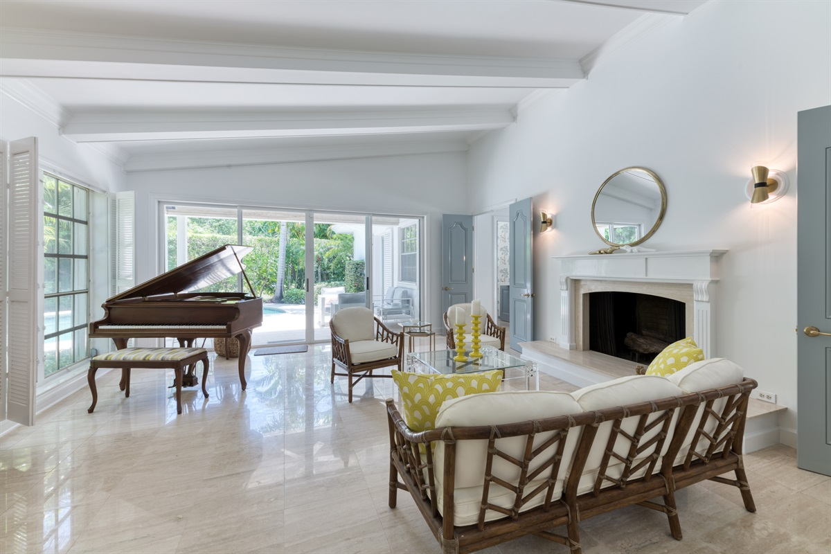 Our formal living room with magnificent large window views of the pool deck, grand piano. decorative fireplace and brand new rustic living room furniture and stunning high backed yellow designed chairs.