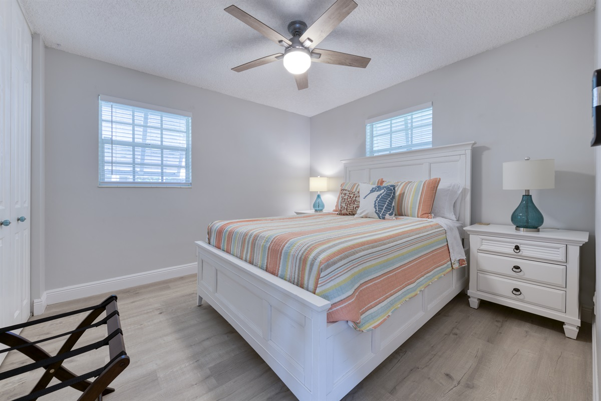 Beautiful second bedroom with Queen bed in hues of pink and teals.