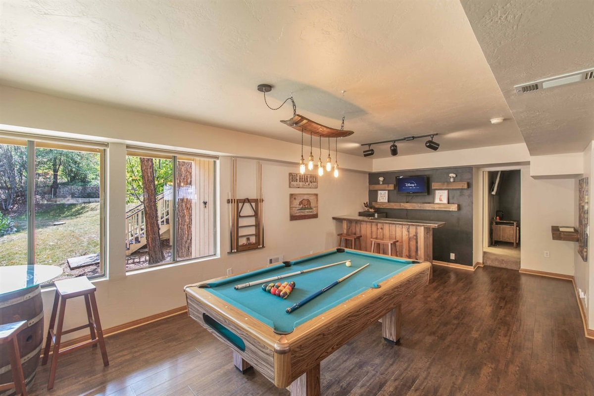 The Game Room has a pool table, a foosball table, a bar, and lots of seating for guests.