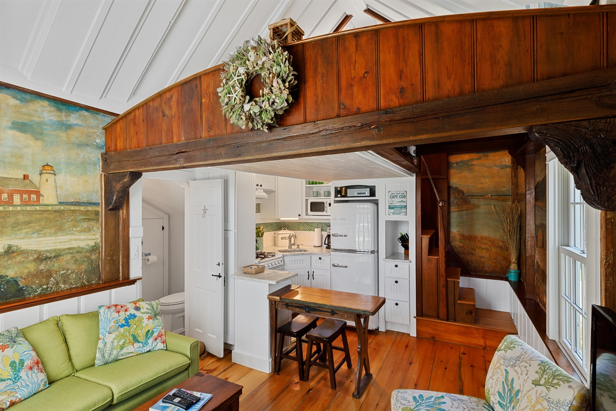 Nautically inspired transom sits atop a large shipwreck salvaged beam with original ship's knees and iron nails serving as architectural corbels in this one of a kind cottage. The original 7 stairs to the bunk loft are rather steep.