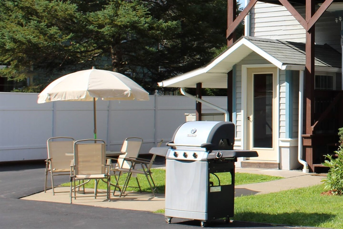 Shared patio area with gas grill for dining and conversation