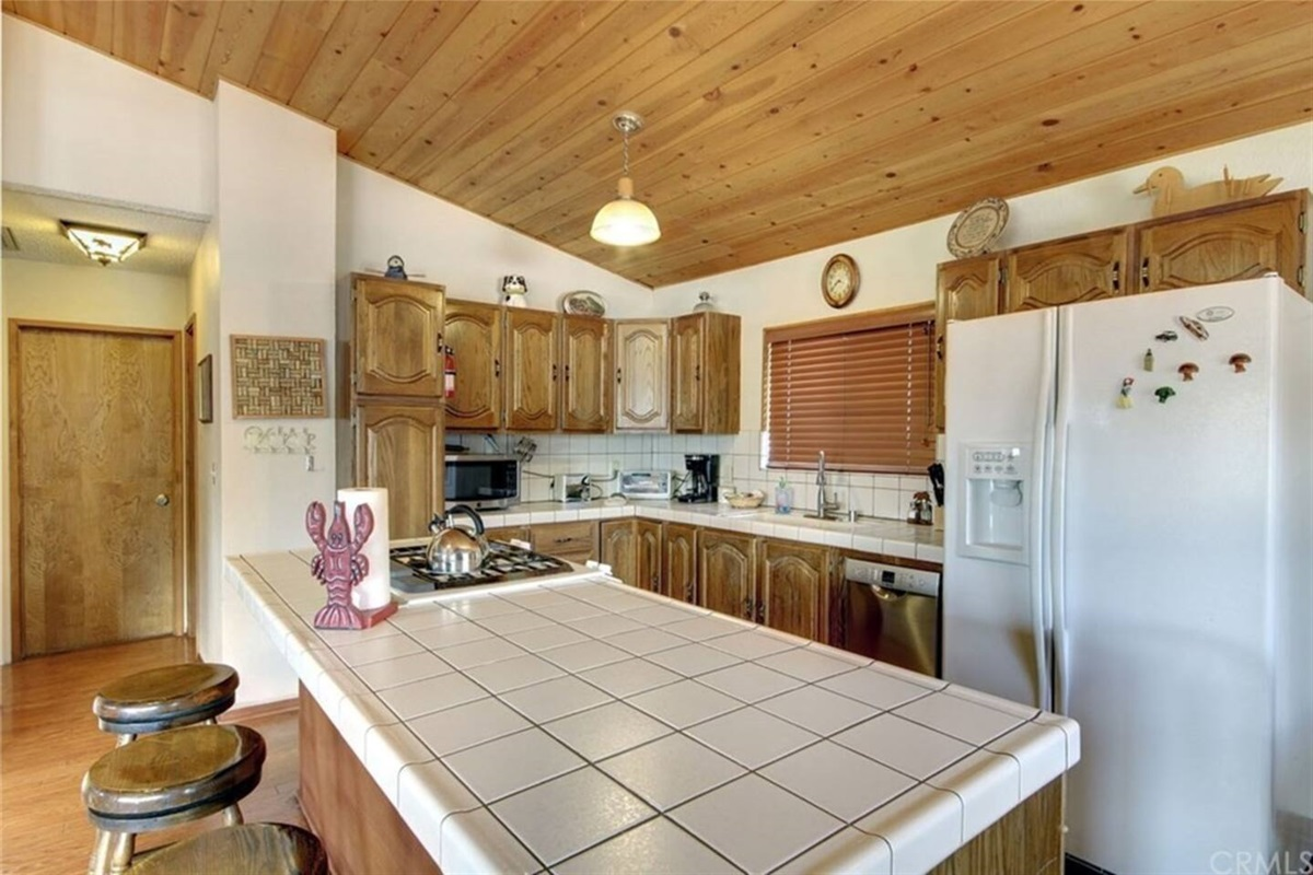 Kitchen: Upstairs open-concept & fully-stocked kitchen includes dishwasher, coffee maker, refrigerator, gas range, microwave, toaster, & big island with 4 barstools.