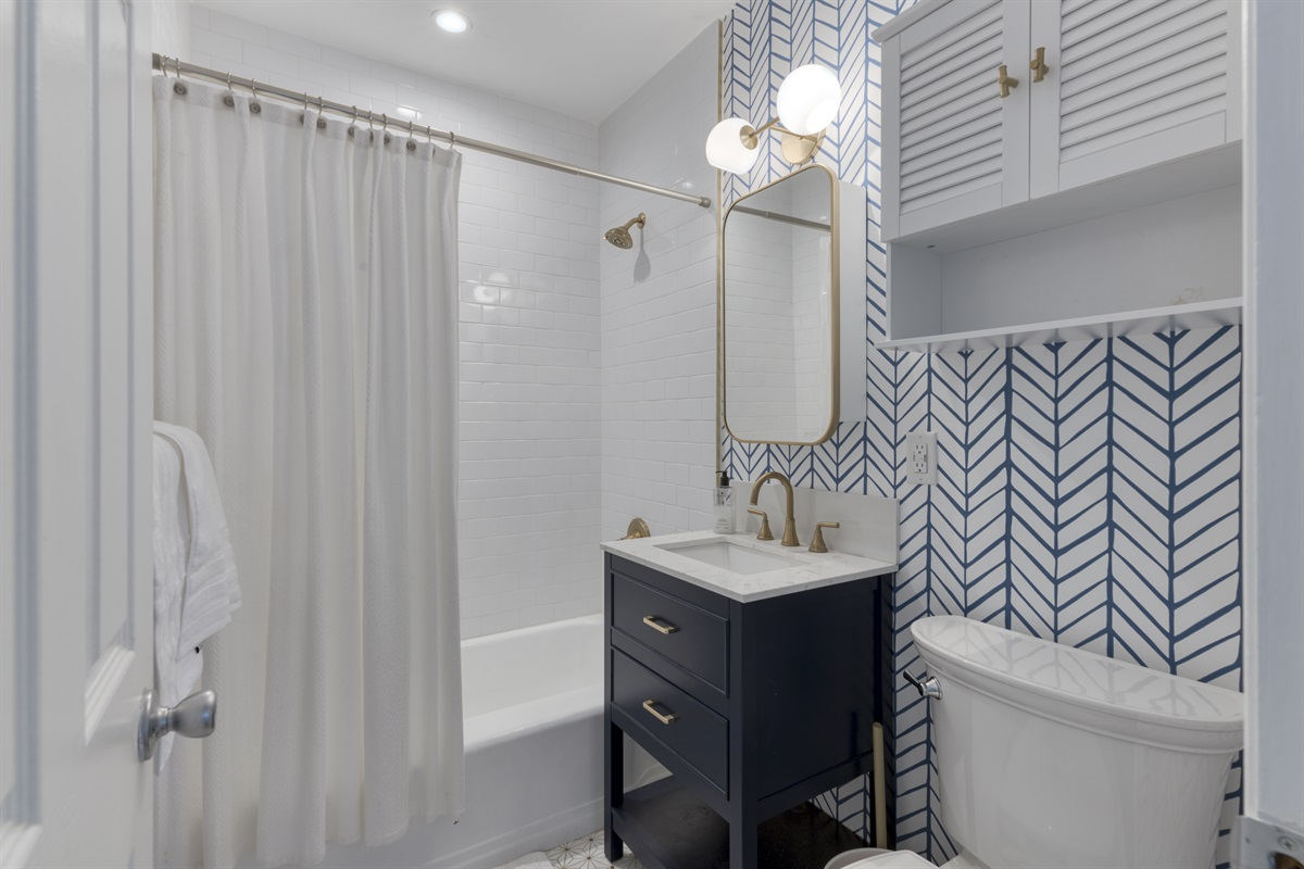 1st Bathroom with combination tub & shower, gold fixtures and funky wallpaper. This bathroom is shared between the bedrooms.