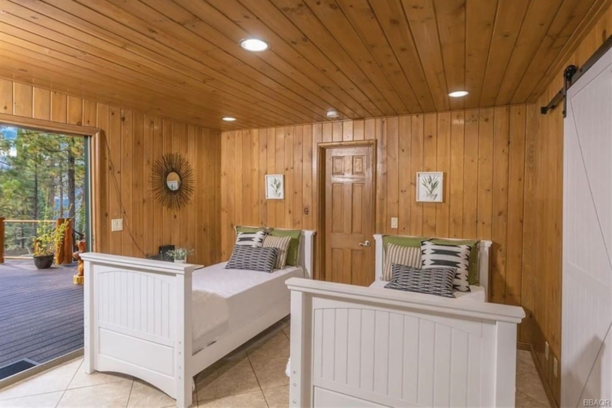 Bedroom #4 (Lower Level): It features 2 twin beds, access to deck, and ensuite bathroom with shower.