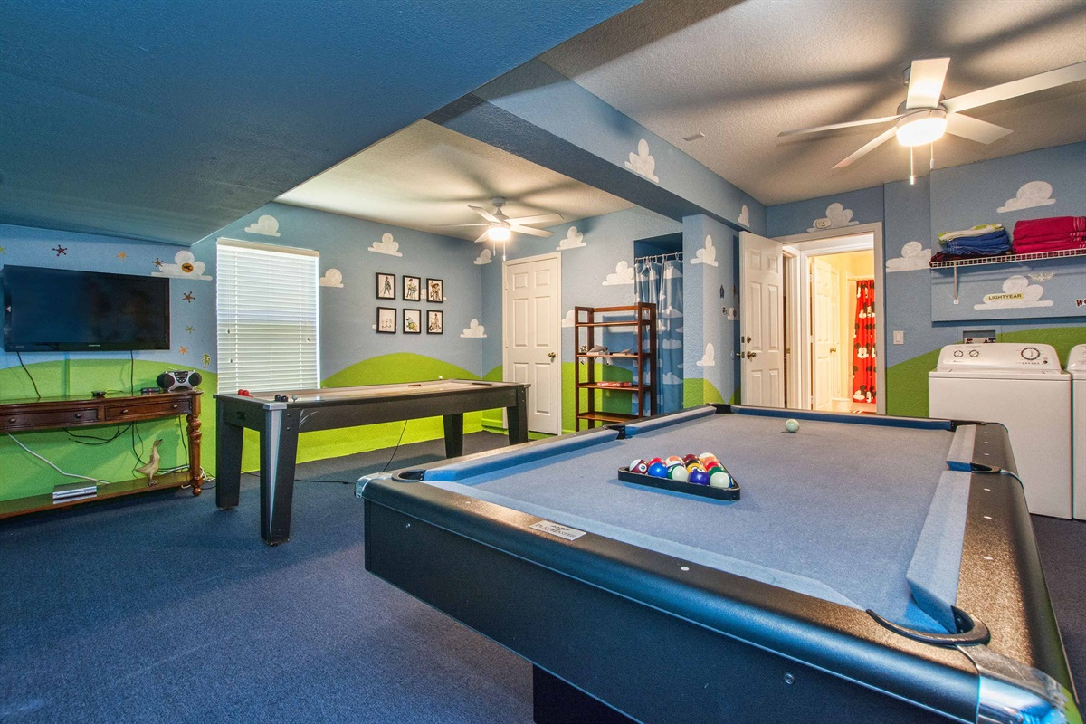 Toy Story game room with billiards, air hockey and TV.