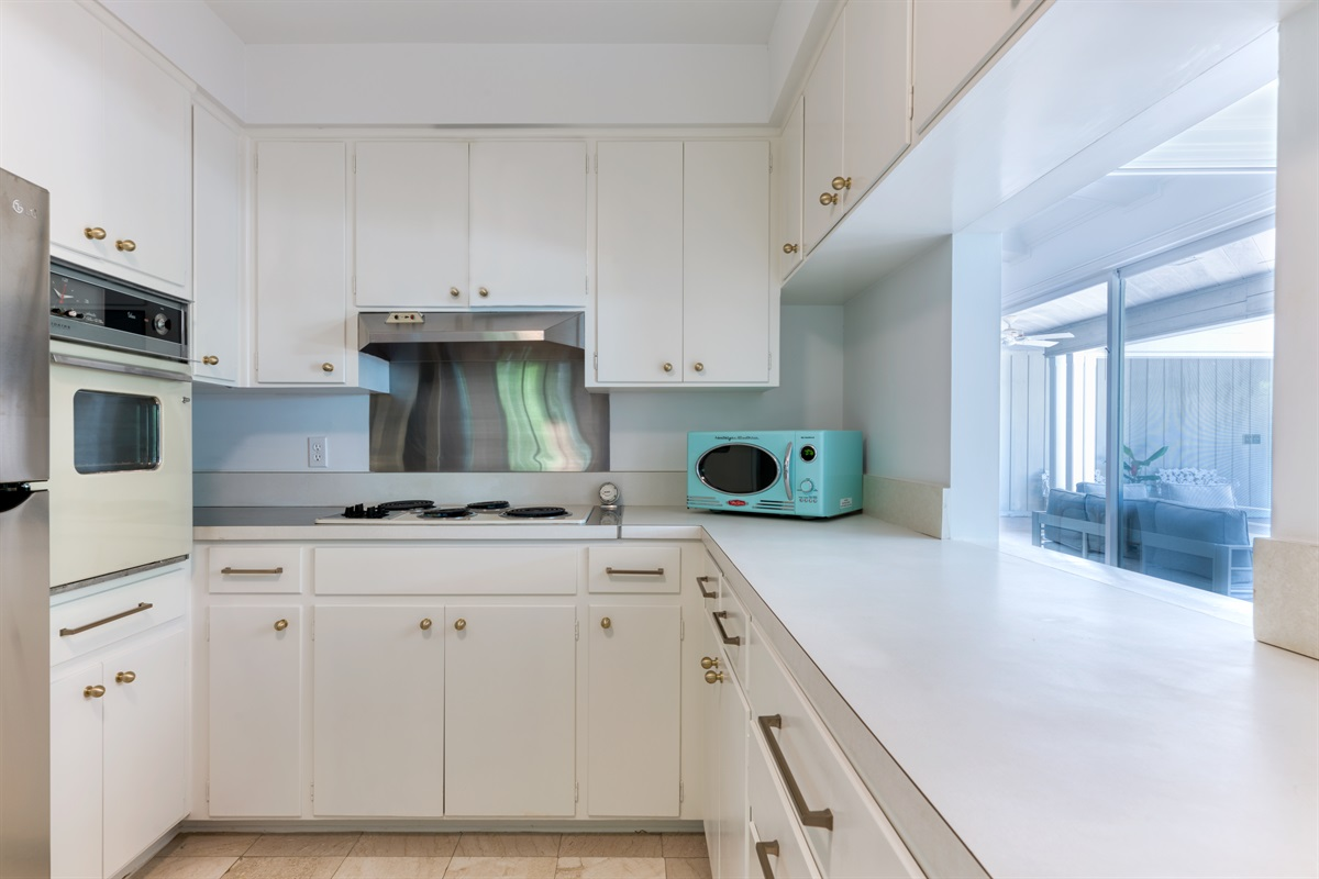Crisp white kitchen with Retro- style and upgraded stainless steel appliances, new gold knobs and pops of Aqua blue. Everything you need to create that oustanding meal to feed the hungry family.