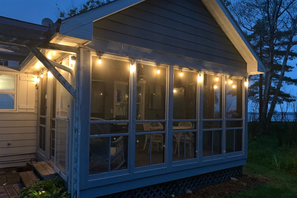 Even the screened in porch on the back side of the cottage has a view of the bay! Enjoy coffee in the morning or wine at night on in the enclosed porch!