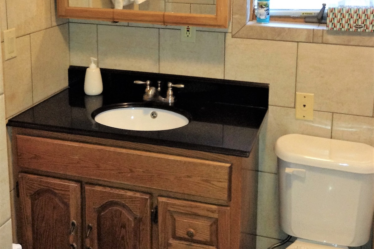 Modern, fully tiled bathroom with granite countertop and lots of storage space.