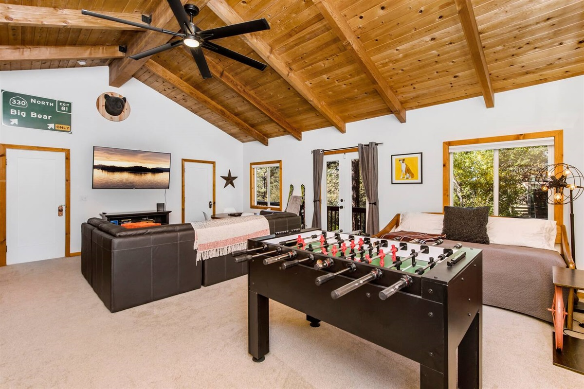 """Bedroom #1/ Family Room/ TV Game Room (Lower Level): Big bedroom has 6 beds to sleep 8 people, foosball, game table, and 65"""" Roku smart TV with sitting area."""