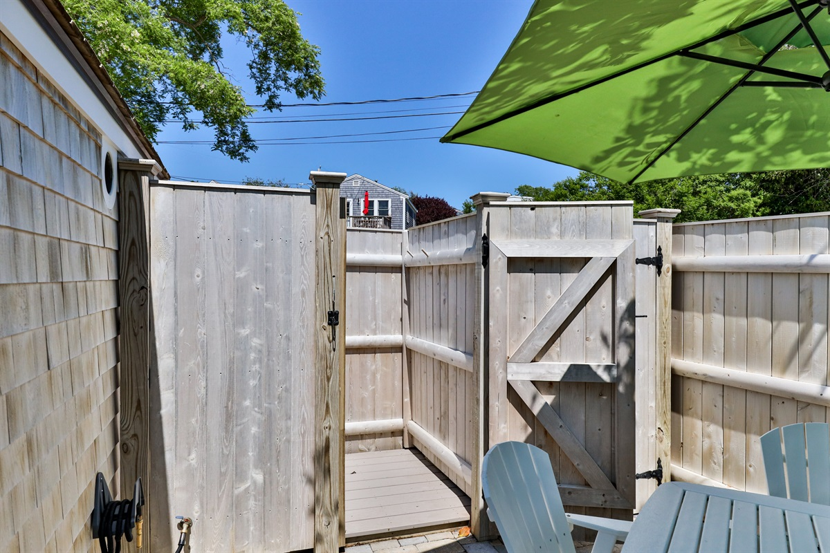 A sunny and roomy outdoor cedar shower with Trex decking is adjacent to the Artist Cottage's patio.