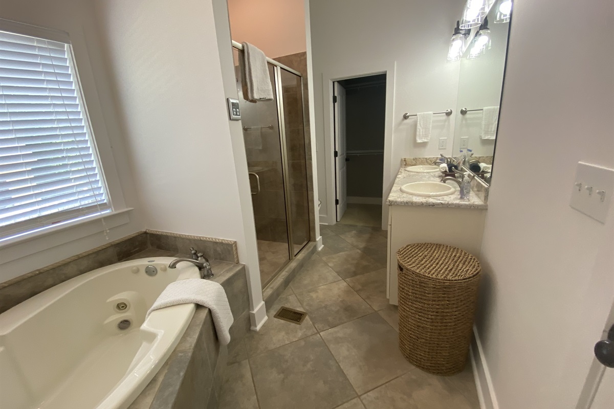 Master En-Suite bathroom features double vanity, jetted tub and stand up shower. We provide fresh white towels and travel size bathroom essentials.