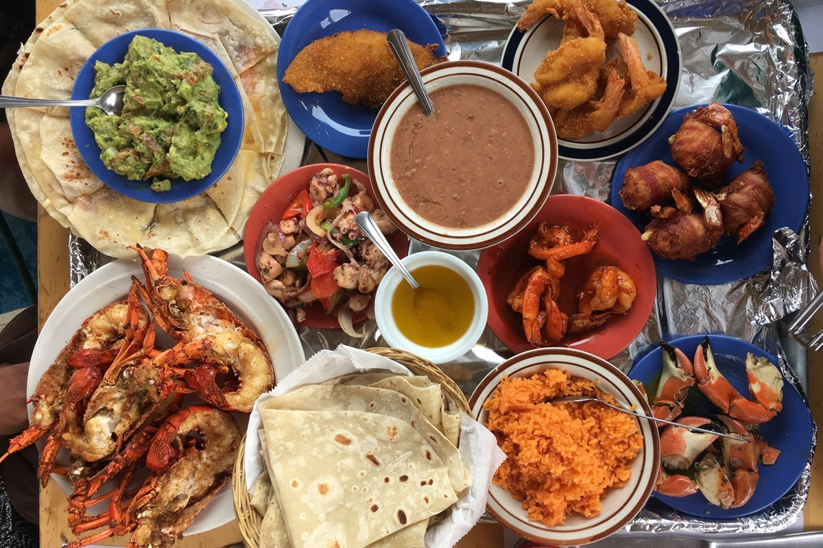 A typical meal in Puerto Nuevo: fresh tortillas, lobster, guacamole, rice, and beans