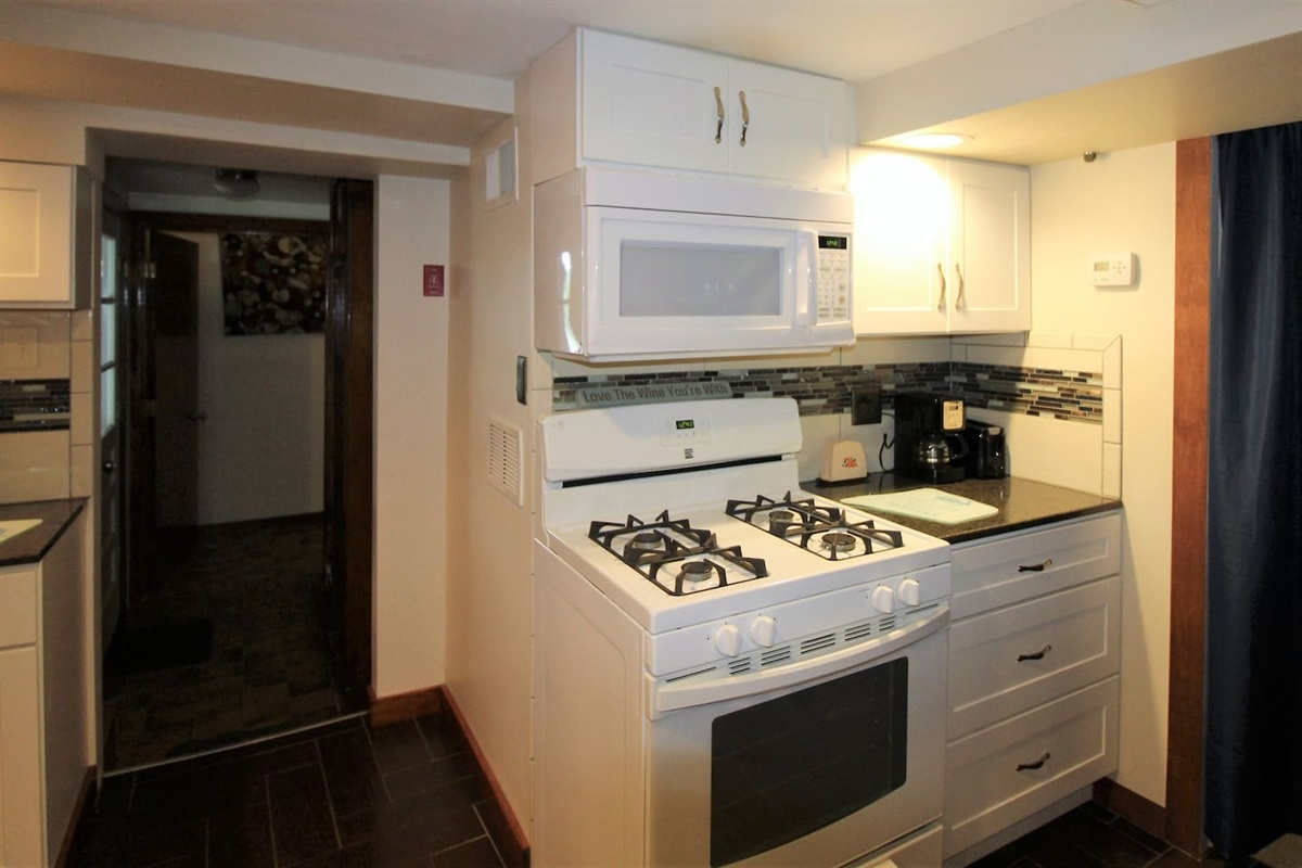 Cozy kitchen space with gas range and microwave