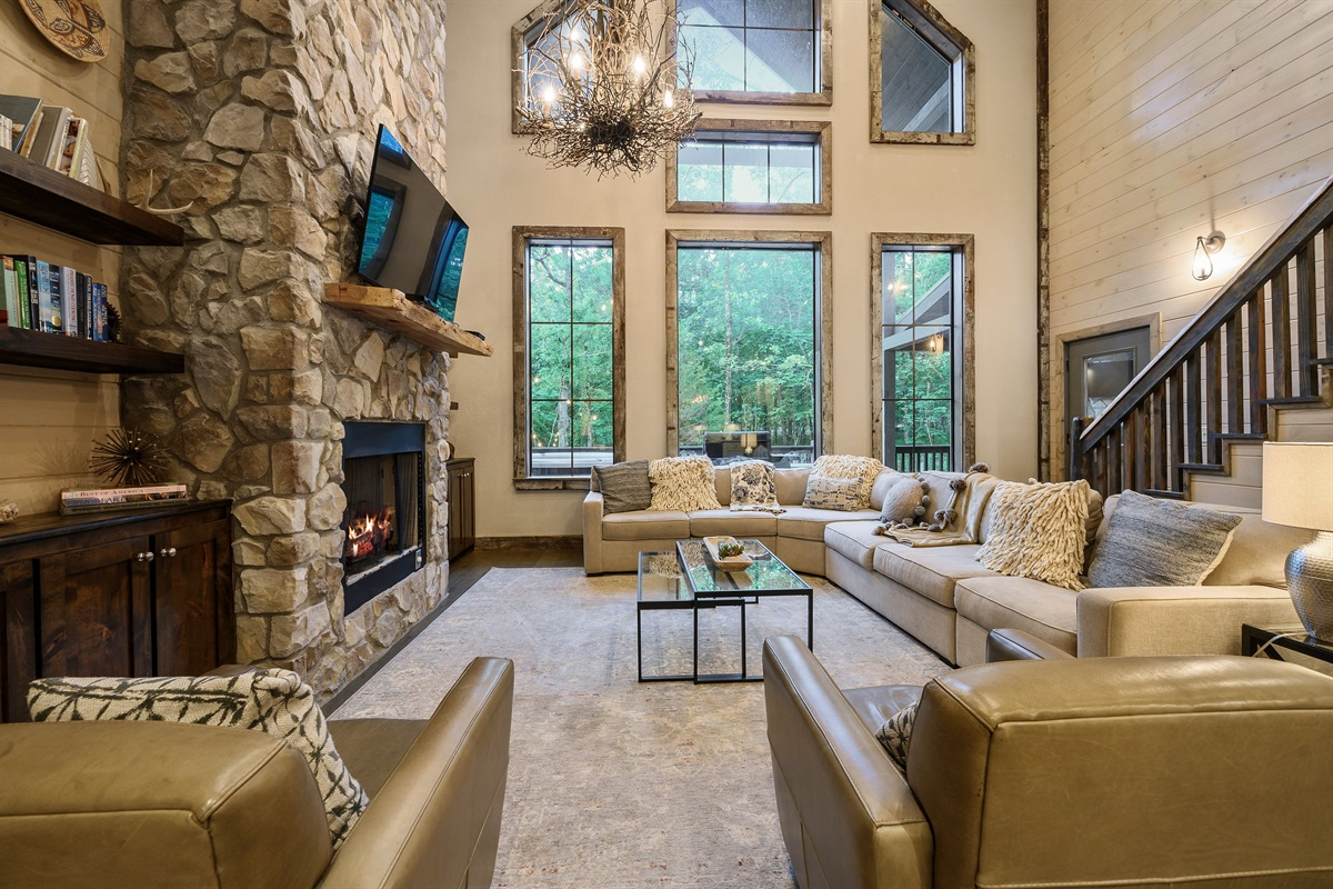 Inviting and cozy living area with gas fireplace, cable and smart TV, plenty of seating and vaulted ceiling and wall full of windows
