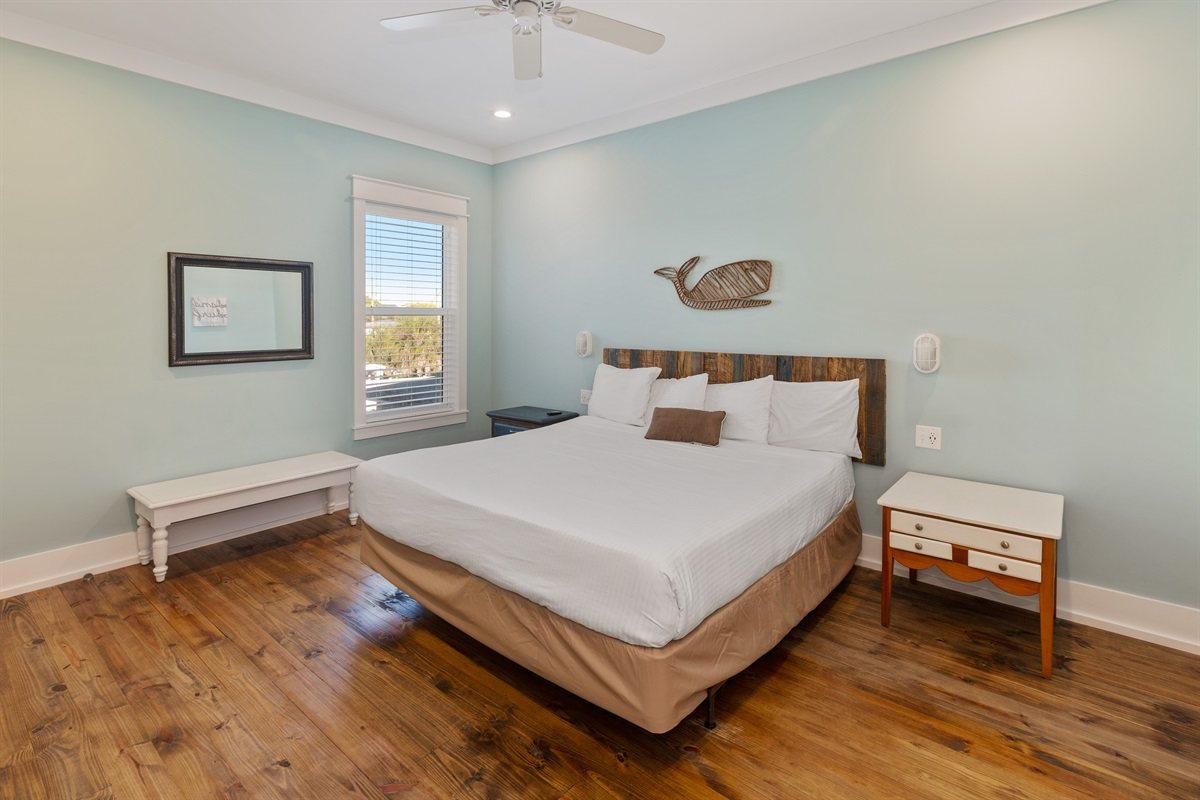 Second floor king suite with private bath. Although the view here is of a whale over the bed, it is the blue crab on the opposite wall that gives this room is namesake the Crab room.
