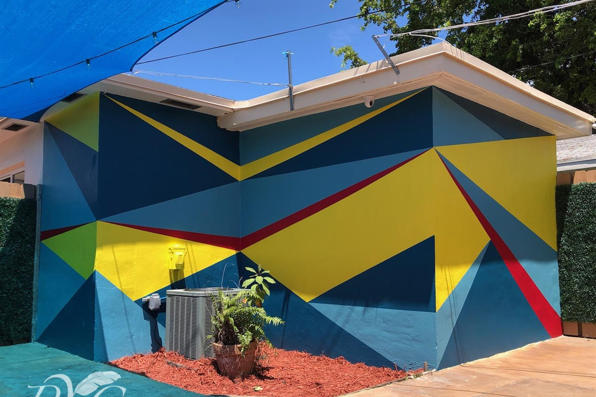 Our new one-of-a-kind Bauhaus inspired mural in the private back patio area! Its geometric shape and colors are the perfect backdrop for your outdoor relaxation.