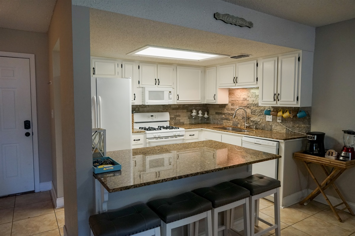 Kitchen w/open views of living area and back deck