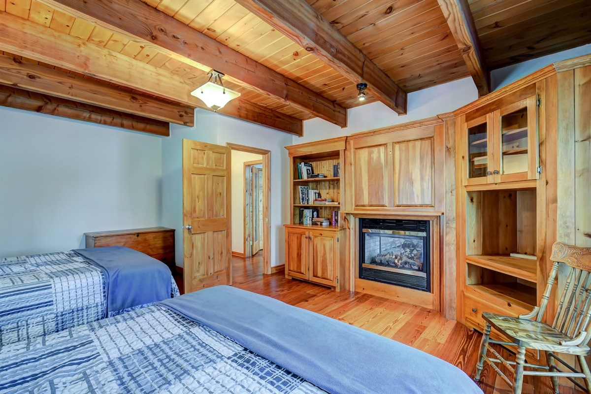 Main floor bedroom with 2 queen beds and propane fireplace