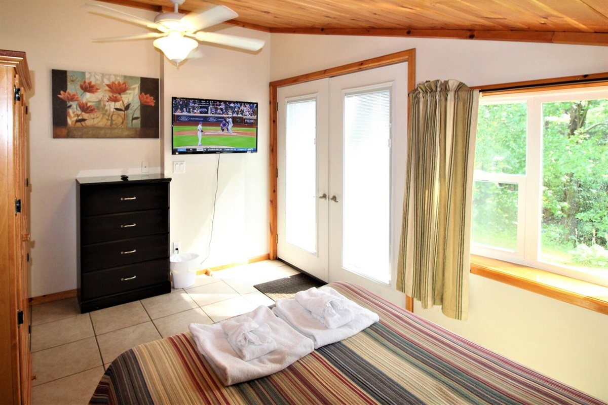"""Bedroom #1 with full size bed, wet bar, views of the lake and a 43"""" (or larger) flat screen smart Roku TV"""