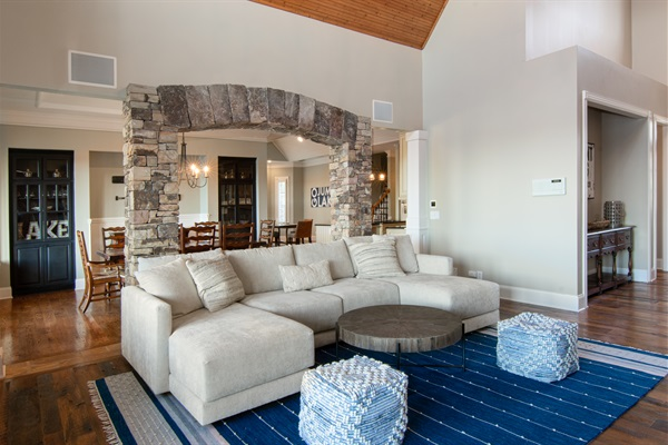 Living room boasts amazing lake views, fireplace, TV. Open to dining room