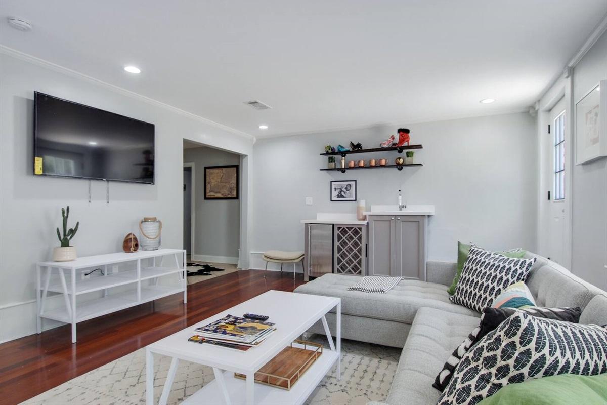 Living room with sleeper sofa, wet bar, big screen smart tv, and rear courtyard access.