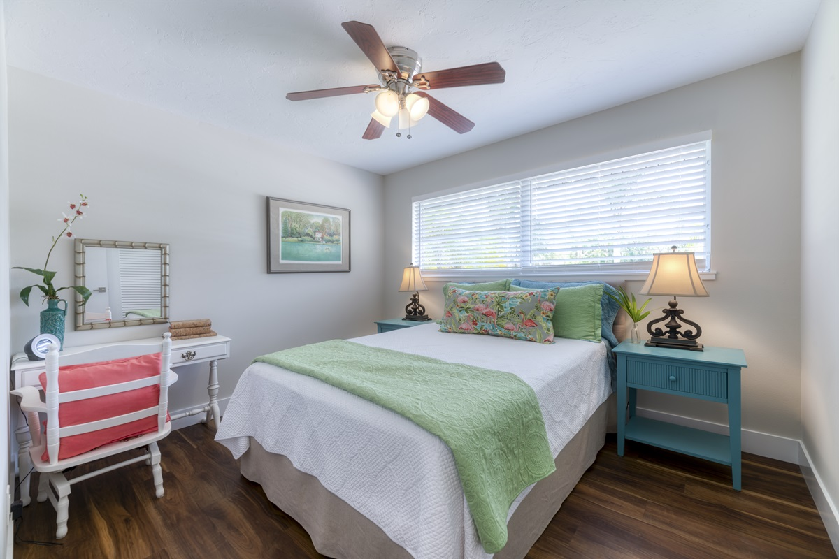 2nd Queen Bedroom with colorful end tables and personal dressing trablee/ desk for remote learning. Rays of natural bright light fill the room. Enjoy the best nights sleep in the comfy bed!