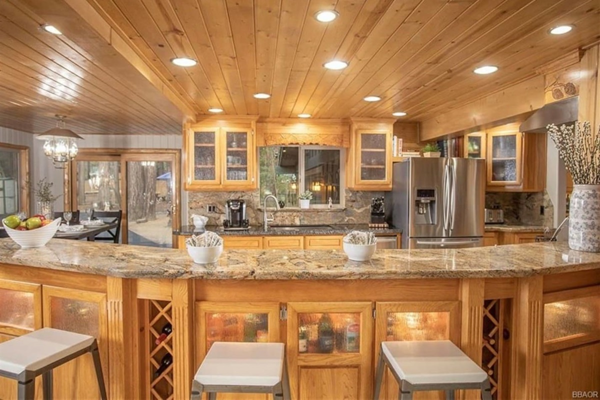 Kitchen: Large island with breakfast bar seating and custom granite countertops.