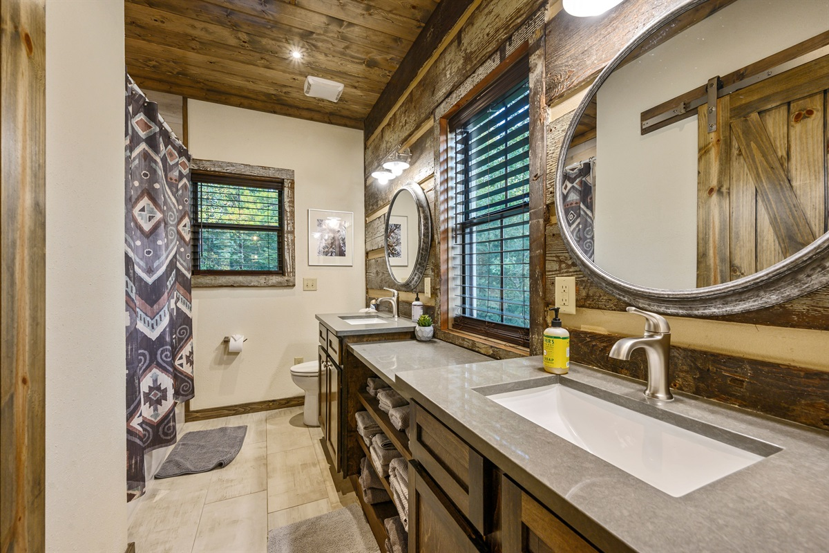 Upstairs bath is equipped with a double vanity and tub and shower combo